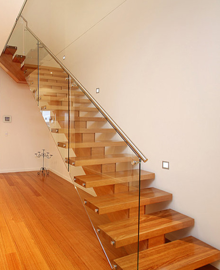 modern staircase with open glass panel side and wooden stair treads