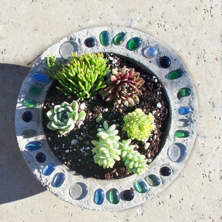 Make a decorative concrete planter with pebble or mosaic