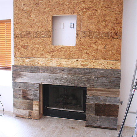 Reclaimed wood fireplace surround adding planks