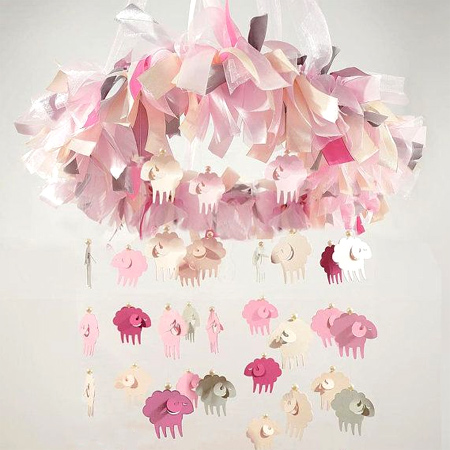 Decorate a gender-neutral nursery with a lamb or sheep theme, pretty pink, grey and white lamp mobile