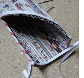 Rolled newspaper wine bottle holder