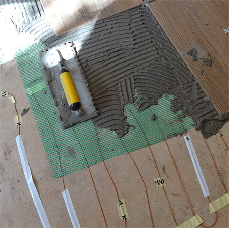 use notched trowel to apply tile adhesive to floor