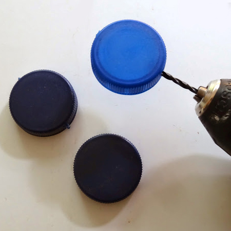 drill a hole top and bottom of plastic bottle caps and thread nylon line
