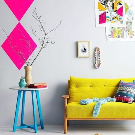 fluorescent neon pink wall decor with yellow couch and blue table