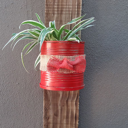 Recycled can plant holder on reclaimed wood stand and painted with rustoleum 2x satin poppy red spray paint