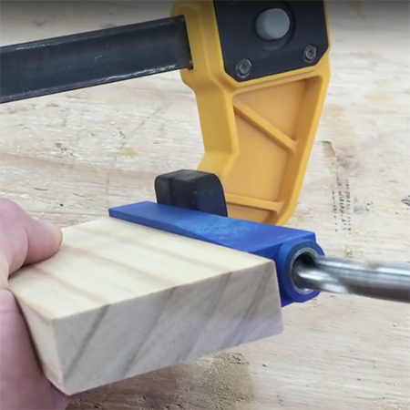 2. Place the jig against the end of your block of wood and clamp firmly in place.
