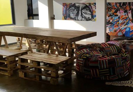 An indoor dining table of reclaimed pallets, with bench-style seating and comfy bean bag seat at the ends of the rectangular table.