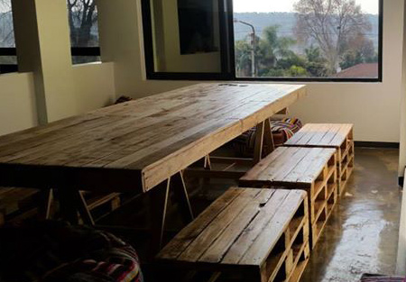 indoor dining table of reclaimed pallets, with bench-style seating