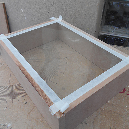 4. A thin strip of masking tape was placed around the edge of the glass. This will help when cutting the front frame to fit and allow the front frame to overhang on both the inside and outside of the box.