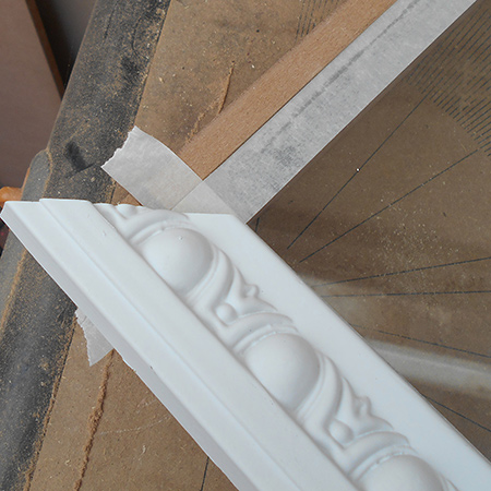 5. Cut one end of the pine moulding or polystyrene cornice and place at the corner of the tape.