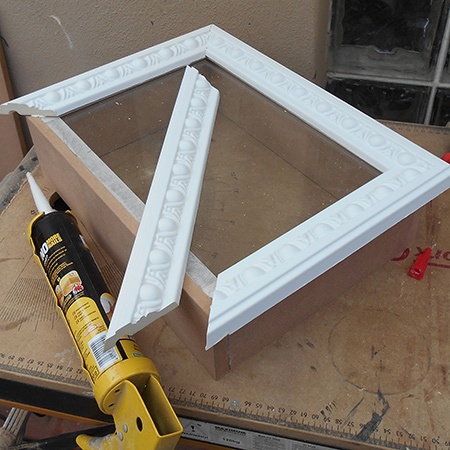 7. Glue the front frame by applying a liberal bead of adhesive to the top edges of the box and also to the edges of the moulding. Press the frame or moulding firmly in place making sure the edges are nicely joined together.