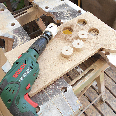 Use a corded drill (500W) to cut out support plugs for the PVC pipes using a 44mm diameter hole saw