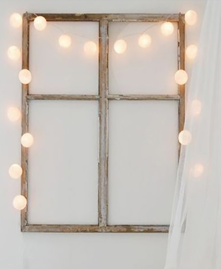 an old window frame is wrapped with a string of fairly lights covered with ping pong balls to make a feature piece.