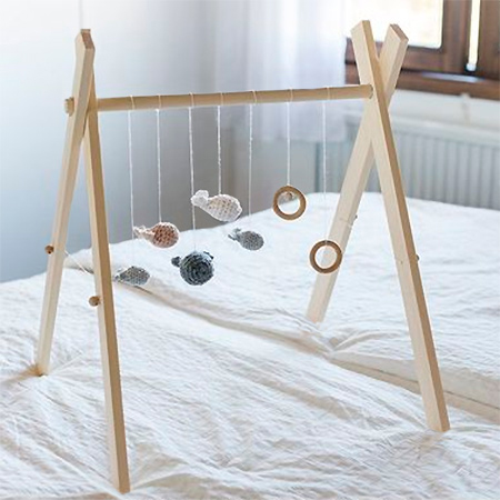 This simple wooden pay mobile won't cost much to make and you can add colourful eye-catching items to keep your little one occupied.