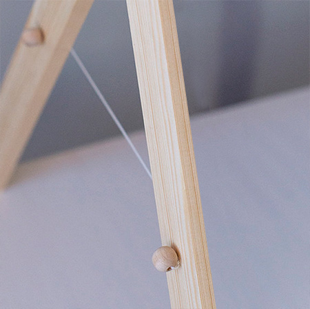 6. At the bottom 130mm centre mark, drill a 3mm hole. Tie one wooden bead to the end of a length of string, thread through the front of a hole in one leg, and through the back in the second leg. Repeat for the other side. Thread a wooden bead and tie off to create a string holder the both sides.
