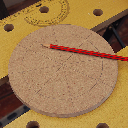 6. Use a pencil and ruler to divide each circular board into eight segments.