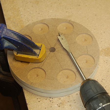 GOOD TO KNOW: Place one board on top of the other and clamp in place. After completing the first hole, switch the boards around. This will prevent chipping around the edges.