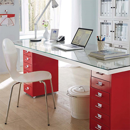 This modern desk is made using a couple of secondhand filing cabinets, a glass top, and an inexpensive hollow core door.
