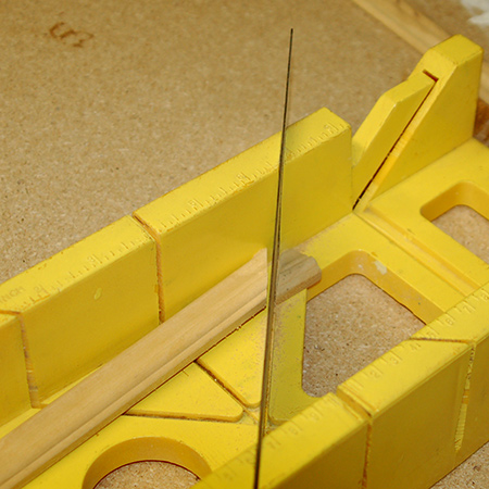Use a mitre saw or mitre box to cut the moulding that fits on top of the frame around the centre opening.