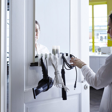 If you are handy with tools, make a cut out shelf to fit under a door- or wall-mounted mirror that allows you to hang your hair styling tools rather than keeping them lying around.