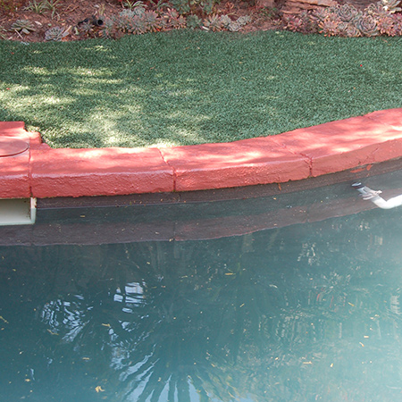 Prominent Paints paving paint is applied to the pool surround to cover up hard water and mineral deposit stains.