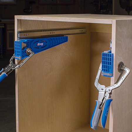 The Drawer Slide Jig consists of two brackets that clamp in place inside the cabinet one on each cabinet side
