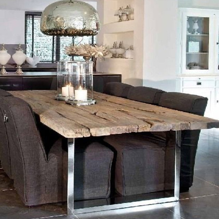 A reclaimed wood table top mounted on a chrome steel base mirrors the mirror-finish pendant lamp above the table
