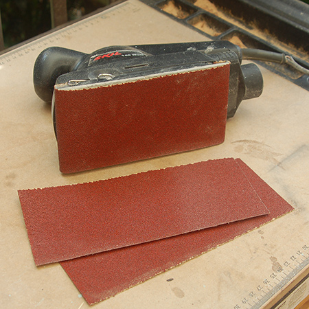 sheet of sandpaper can be divided into three strips for fitting onto the base of the sander
