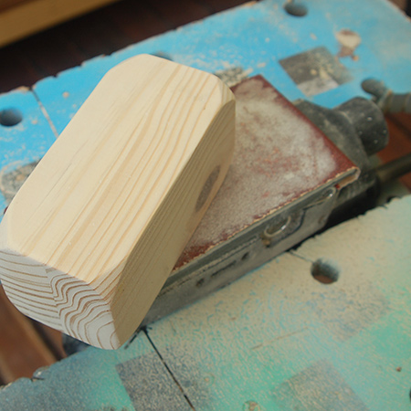 Lock your sander upside down in a clamping workbench. In this way you can use both hands to move the project around on the sandpaper