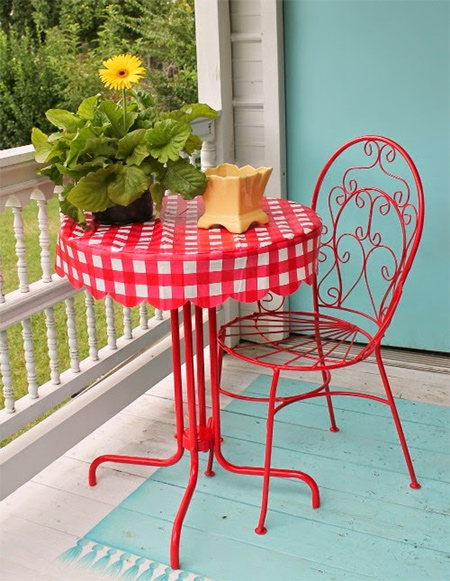Left out in the trash, this bistro table and chair gets repurposed and upcycled with Rust-Oleum gloss apple red and a vinyl tablecloth.