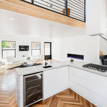 All-white interiors with white furnishings harmonize with the warm wood floors and beams, with black accents scattered throughout for visual impact.
