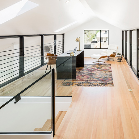 The stairs from the lower to upper level have transparent glass sides and the steel and wire balustrade around the loft provides safety without imposing on the visual flow throughout the open areas.