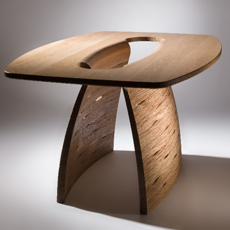 Inspired by naturally occurring geometric forms, John Lee explores the enhancement of timber's natural properties whilst experimenting with form, function and finish. Lee's designs explore textured finishes by working the natural grain patterns of raw timber into his dynamic forms. The 'Pegasus Table' is solid oak with a hand carved base.