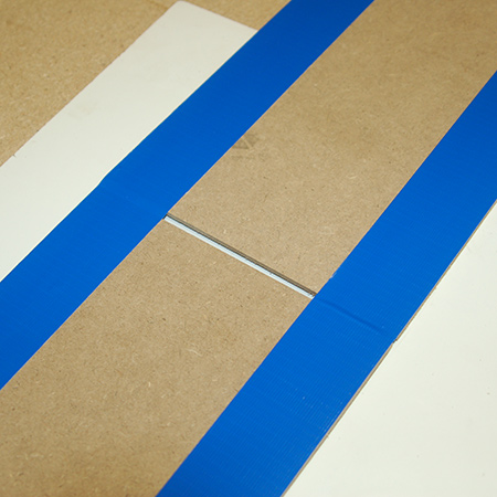 3. Lay strips of duct tape from the top of one panel to the bottom of the other, ensuring that the 5mm gap remains.