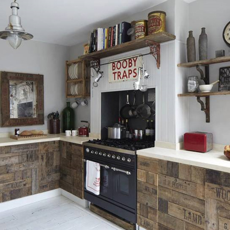 This rustic kitchen features a variety of reclaimed wood products. Love the crates and pallets repurposed as kitchen cabinet doors