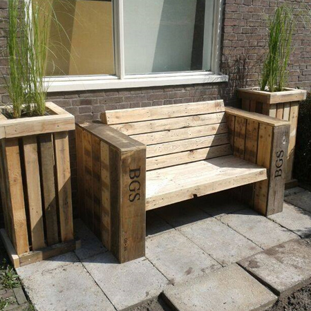 Reclaimed wood pallet bench is framed by pallet flower boxes
