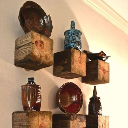 Reclaimed fence posts or wood beams are cut down to size to make wood shelves to display a variety of collectibles.