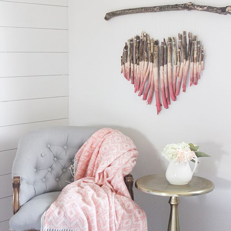After trimming back trees or large shrubs, using these to make unique decor for the home is fun and adds a unique feature to any wall. The heart-shaped wall decor below is given a pink ombre paint treatment and suspended from a larger branch on thin string.