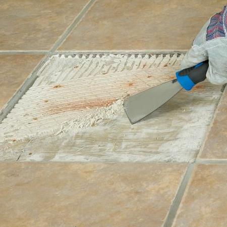 4. Use a paint scraper to remove any hardened old adhesive off the floor. Hard areas can be gently tapped with the hammer and chisel to loosen.