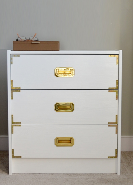 Sometimes all it takes is a coat or two of paint, new handles, and adding brass corners onto drawer fronts. If you are unable to find brass corners, use steel corners and apply a coat of Rust-Oleum metallics brass spray paint.
