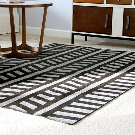 Here's an easy way to add a new look to a plain, expensive low-pile, coir, sisal or jute rug. All you need is some paint and masking tape!