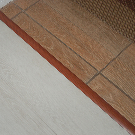 You need to fit a carpet or tile edging strip to cover up where different floor finishes come together. In this case I went with a brown tile profile wide enough to cover and even the gap.