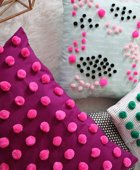 Pom-poms small or large add colour, interest and texture to plain cushions