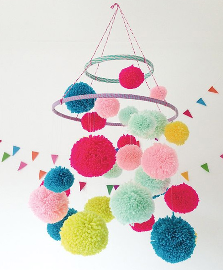 Use embroidery hoops and colourful pom-poms to make a unique mobile for a nursery