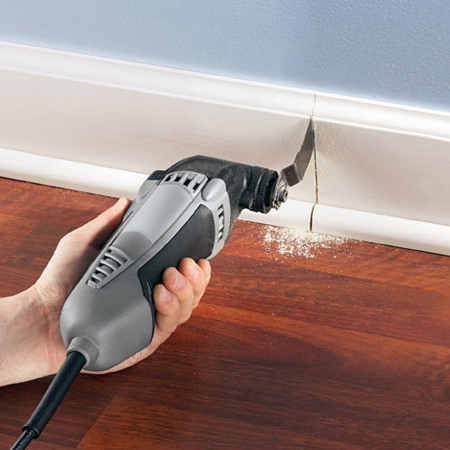 Use a flush-cutting wood blade attachment. Hold the blade flat against the flooring and plunge-cut.