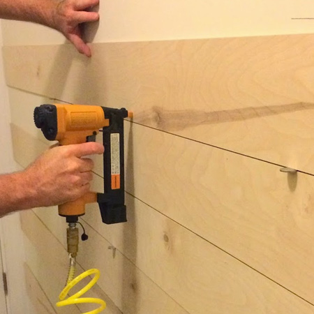 Use a pneumatic brad nailer to attach planks or board to a backing board or drywall.