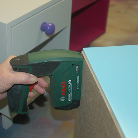 HOME-DZINE | DIY Furniture - Secure the back with a Bosch Tacker and staples, or use a hammer and panel pins. Remember to angle the panel pins when hammering in to better hold the backing in place.