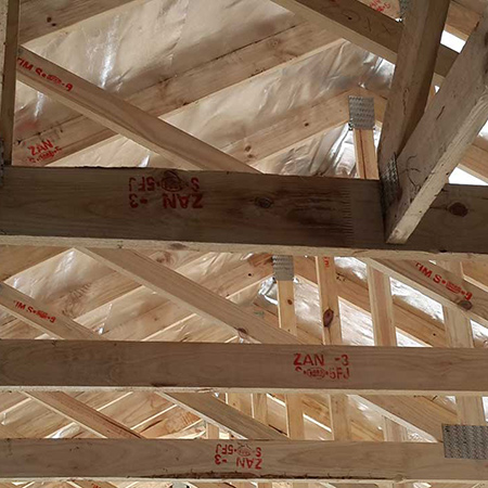 Truss hangers not installed due to a mix-up with a different section and detail.