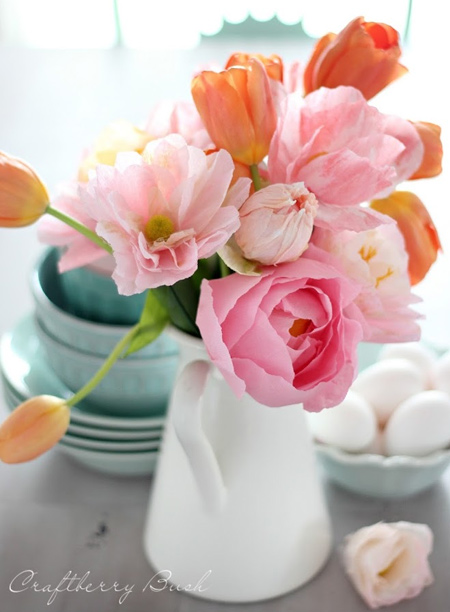 Use crepe paper flowers to add a splash of colour to your dining table. This assorted display of palest pink crepe paper flowers adds interest to a few tulips.