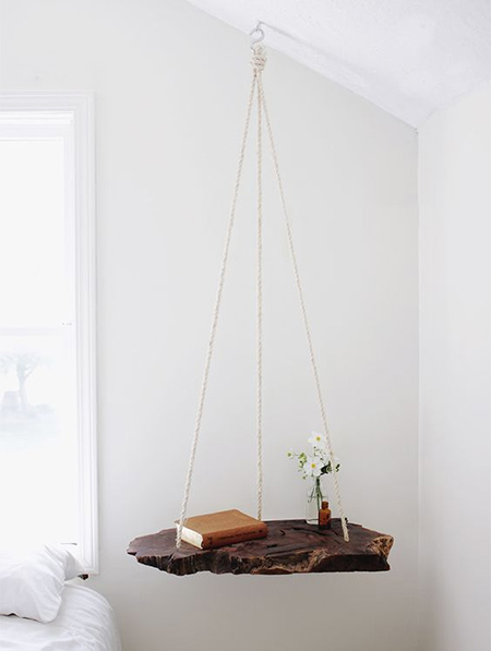 In a bedroom where space is limited, a hanging table takes up absolutely no floor space and is an easy DIY solution that you can make in an hour or two using a variety of materials.